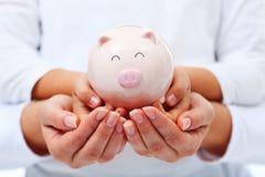 Финансовая концепция образования - руки взрослого и ребенка держа pigg Стоковая Фотография RF