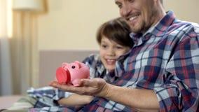 Piggy-τράπεζα εκμετάλλευσης μπαμπάδων και γιων και χαμόγελο, κοινωνική πρόνοια, ασφάλεια υγείας στοκ εικόνες με δικαίωμα ελεύθερης χρήσης