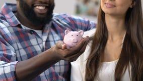 Piggy-τράπεζα εκμετάλλευσης ανδρών αφροαμερικάνων, γυναίκα που βάζει το νόμισμα μέσα, προϋπολογισμός απόθεμα βίντεο