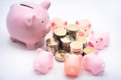 Piggy τράπεζες μαμών και μωρών και σωρός των νομισμάτων στοκ εικόνες
