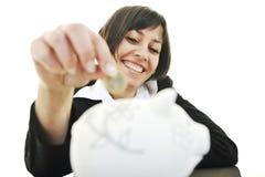 Επιχειρησιακή γυναίκα που βάζει τα χρήματα νομισμάτων στη piggy τράπεζα Στοκ Εικόνες