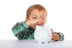Мальчик кладет деньги в piggy банк Стоковая Фотография