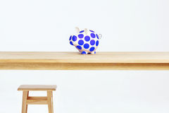 Piggy. Stands on a wooden table, a stool next to Royalty Free Stock Photo