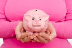 Δύο χέρια κρατούν μια piggy τράπεζα Στοκ Εικόνες