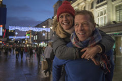 Piggy Back Through Festive City. Mature men is giving his wife a piggy back through the city centre at Christmas time Stock Photos