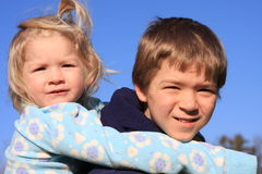 Piggy back ride. Older brother giving younger sister a piggy back ride stock photo