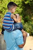 Piggy back ride father and son. A father gives his son a piggy back ride on his shoulders Stock Photo