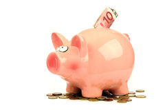 Piggy bank. Pink piggy bank with some money to go with it Stock Photo