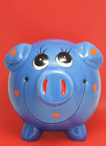 Piggy bank. Blue piggy bank on red background Stock Image