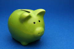 Piggy bank. A green piggy bank on blue background, shot slightly from the side Stock Images