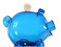 Piggy Bank. Silver coin perched on top of an empty, clear blue piggy bank. Isolated on white royalty free stock photo