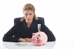 Piggy bank. Business lady sitting at her desk in front of a piggy bank with one hundred dollar Stock Photography