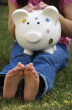 Piggy bank. A little girl sitting in the grass holding her piggy bank with bare feet Royalty Free Stock Photography