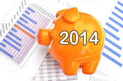 Piggy bank with 2014 text. Piggy bank on a financial report Royalty Free Stock Image