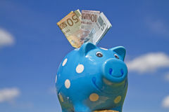 Piggy bank. And banknotes in front of a cloudy sky Royalty Free Stock Photography