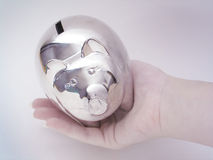 Piggy bank. Hand holding a silver piggy bank Stock Photo