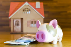 Piggy bank. Banknote and  model of home : Concepts for Saving for home Royalty Free Stock Image
