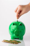 Piggy Bank. Caucasian hand putting coin in green piggy bank, with coins spread in front of the piggy bank stock photo