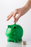 Piggy Bank. Caucasian hand putting coin in green piggy bank, with coins stack in front of the piggy bank stock photography