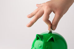 Piggy Bank. Caucasian hand putting coin in green piggy bank, with details on the hand, close up of the scene royalty free stock photos