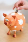 Piggy bank. A hand dropping a coin into a smiling piggy bank Royalty Free Stock Photo