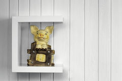 Piggy bank adobe RGB. Pigy bank on c shelf mount on white wooden wall Royalty Free Stock Photo