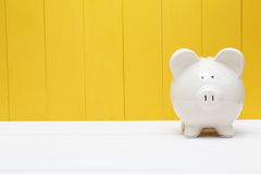 Piggy bank against a yellow wall Royalty Free Stock Image