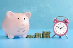 Piggy bank, alarm clock and stack of coins photographed close-up. Cheerful ceramic pig on a blue background. royalty free stock photo