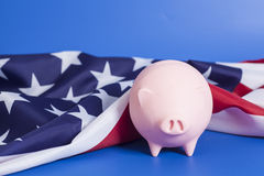 Piggy Bank with American Flag. On blue background Royalty Free Stock Photo