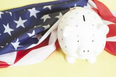 Piggy Bank with American Flag. On yellow background Royalty Free Stock Photography