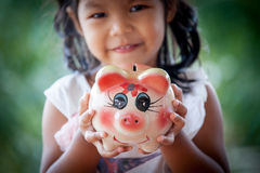 Piggy Bank on asian little girl hand Royalty Free Stock Photos