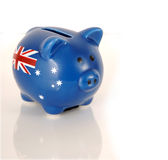 Piggy bank with Australian flag on white reflective surface. Handpainted money piggy bank with Australian flag on white reflective surface Stock Image