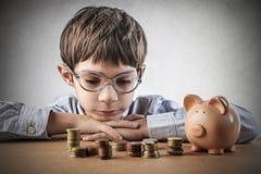 Piggy bank. Baby facing the piggy bank savings Stock Image