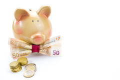 Piggy bank with a banknote bow and coins Royalty Free Stock Photos