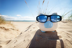 Piggy Bank on beach vacation. Holiday savings piggy bank on a beach vacation with sunglasses Royalty Free Stock Photos