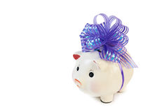 Piggy bank with big violet bow isolated on white Stock Images