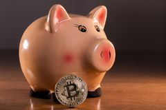 Piggy bank with bitcoin. On top of wooden table Royalty Free Stock Image