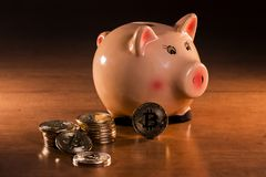 Piggy bank with bitcoins. On top of wooden table Royalty Free Stock Photos