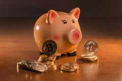 Piggy bank with bitcoins. On top of wooden table Royalty Free Stock Photo