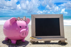 Piggy bank and black board on the beach Royalty Free Stock Images