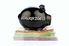 Piggy bank on black money Stock Images