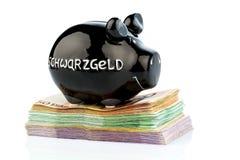 Piggy bank on black money Royalty Free Stock Photos