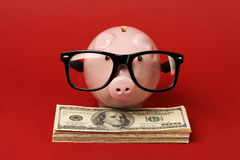 Piggy bank with black spectacle frame of glasses standing on stack of money american hundred dollar bills on red background Stock Photo