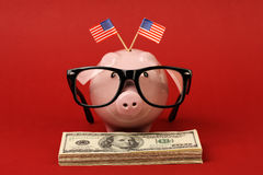 Piggy bank with black spectacle frame of glasses and two small USA flags standing on stack of money american hundred dollar bills. On red background Royalty Free Stock Photo