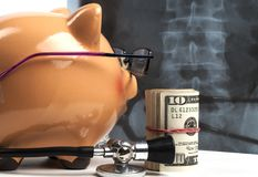 Piggy Bank Xray Exam. Piggy Bank With Black Stethoscope and Dollar Banknotes Roll viewing Xray on White Background royalty free stock image