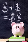 Piggy Bank saving plan growth. Pink piggy bank with glasses standing on books next to a blackboard with simple money math.  Sharp focus on the piggy bank Stock Photos