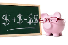 Piggybank with blackboard savings plan calculation. Pink piggy bank with glasses standing next to a blackboard with simple money math isolated on a white Royalty Free Stock Images