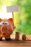 Piggy bank with blank billboard on table and nature vertical Stock Image