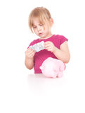 Piggy bank and blond little girl Stock Photo