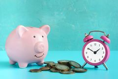 Piggy bank on a blue background. Near a pile of coins and a pink alarm clock. The symbol is the accumulation and royalty free stock images
